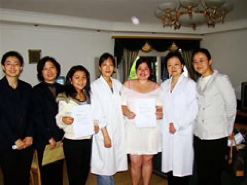 La doctora Nancy (i) entrega a Minneth (chamarra blanca), y a Berenice (vestido blanco) su roomate, la constancia de que están sanas al término de la cuarentena. Como muestra de buena voluntad, el personal médico se quitó los trajes especiales. (Foto: Cor