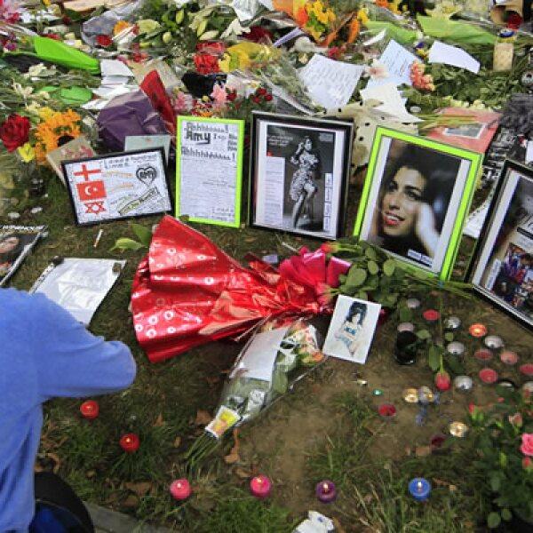 Una mujer coloca velas entre las flores y tributos colocados afuera del departamento londinense donde vivía Winehouse.