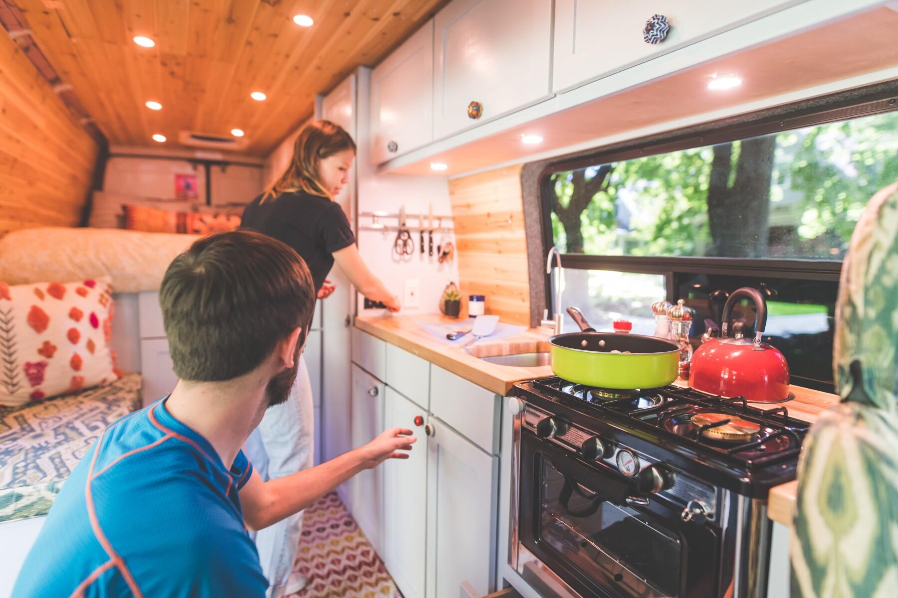 Millennial couple cook breakfast in the van they live in