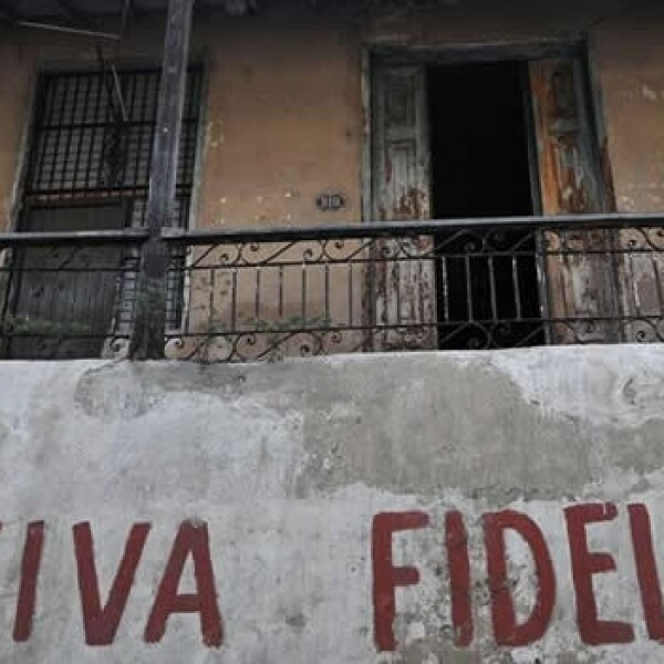 una mujer en el balcón de su casa junto a un grafiti alusivo al líder de la revolución cubana, Fidel Castro