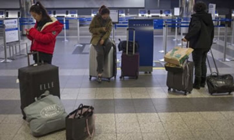 Los viajeros hacen largas filas para poder subirse a un avión debido a las afectaciones por el huracán Sandy. (Foto: Reuters)