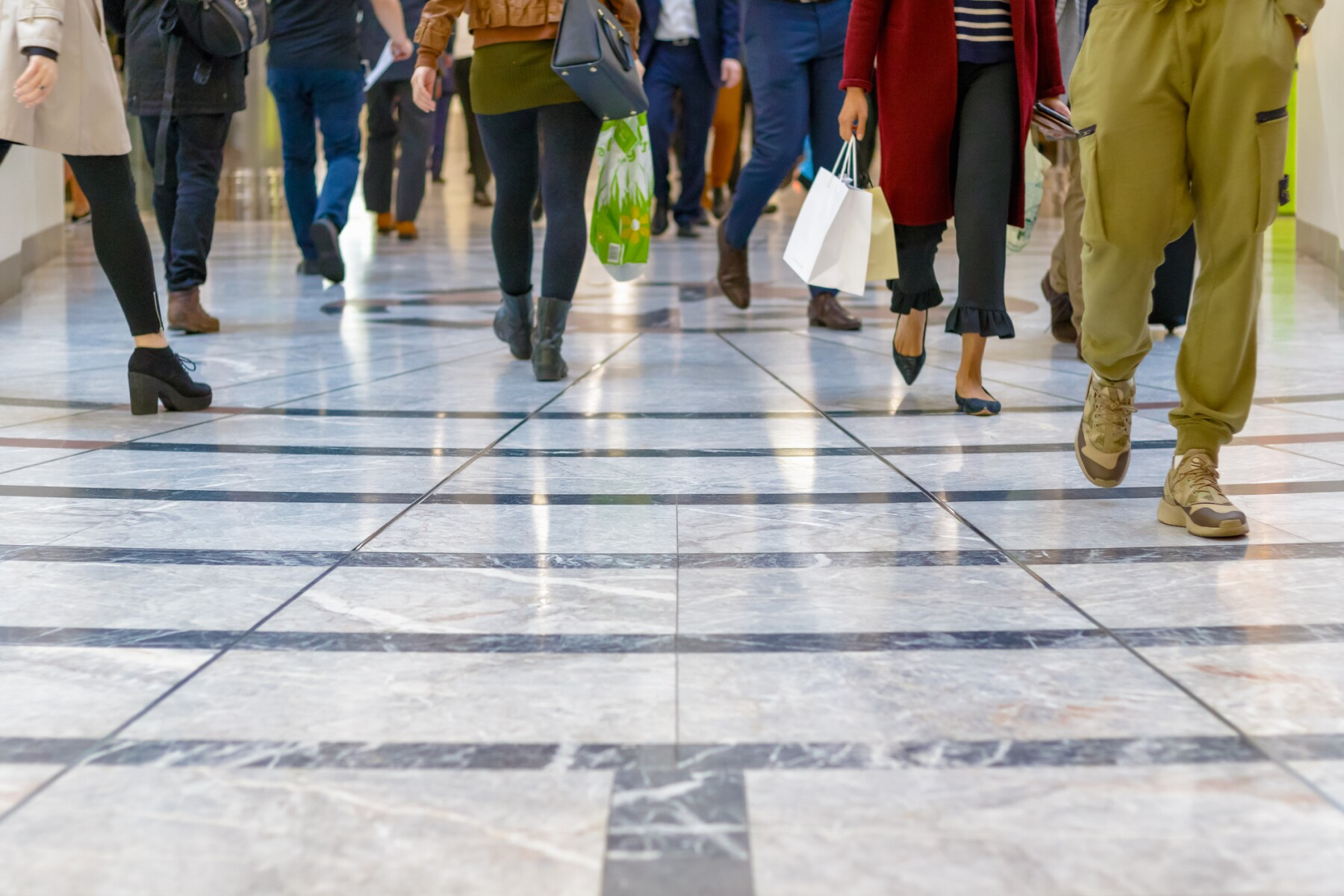 A modern floor with legs of a crowd walking in the background
