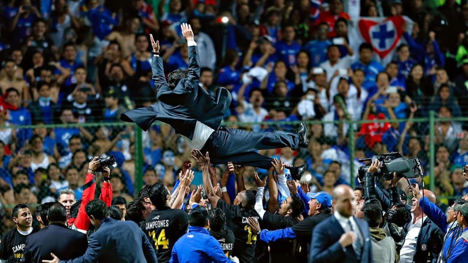 Luis Fernando Tena, director técnico de Cruz Azul, es lanzado al aire por los jugadores