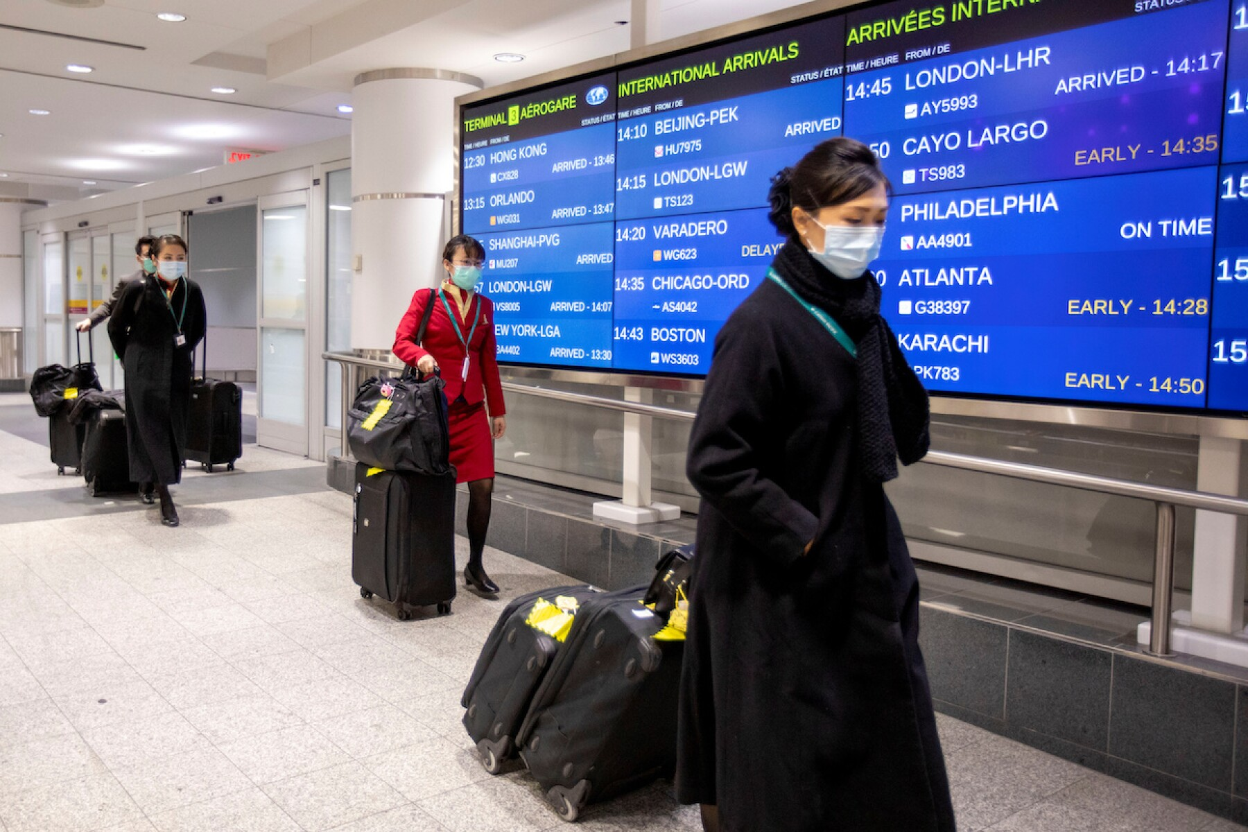 Flight crew members wear masks as they arrive at Pearson airport in Toronto