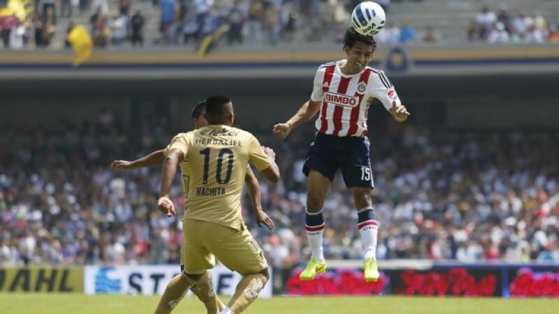 Fernando Arce de Chivas conecta el balón con la cabeza ante la marca de los jugadores del cuadro universitario