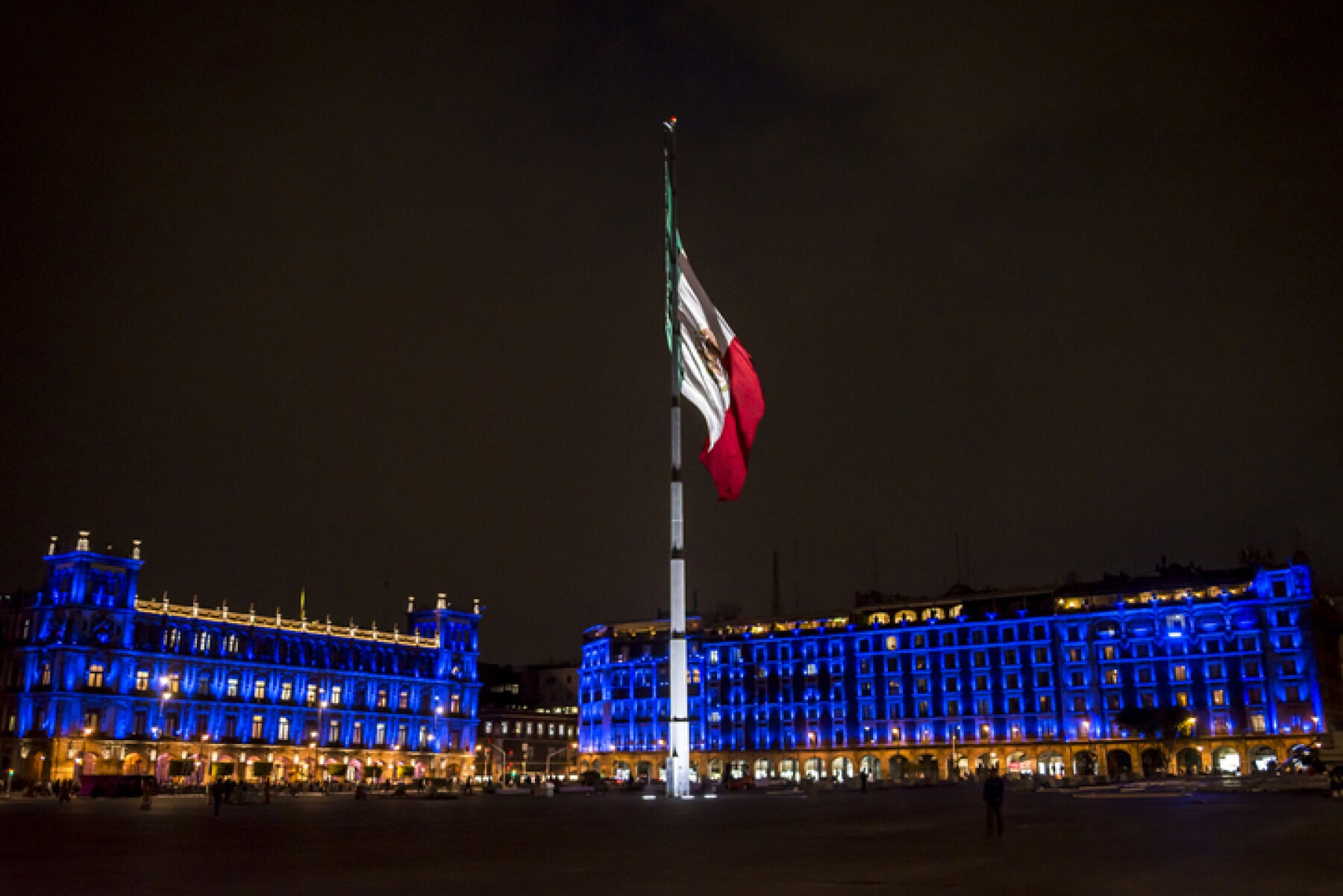 Huge Mexican flag on flagpole at the Mexico City's main square or Zócalo, officially known as the Plaza de la Constitución or Constitution square at night, Mexico City, Mexico