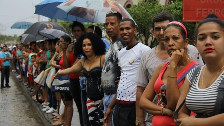 Decenas de cubanos desafiaron las inclemencias del clima y aguardaron el paso de la caravana presidencial en su camino hacia La Habana Vieja