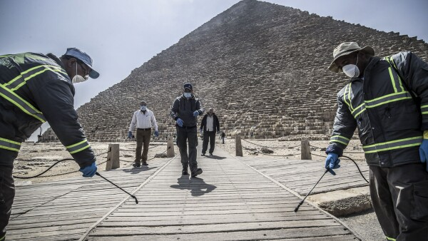 Los trabajadores del municipio egipcio desinfectan la necrópolis de las pirámides de Giza, en las afueras del suroeste de la capital egipcia, El Cairo, el 25 de marzo de 2020 como medida de protección contra la propagación del coronavirus.
