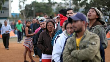 Migrants, part of a caravan of thousands from Central America trying to reach the United States, queue for aid in a shelter in Tijuana