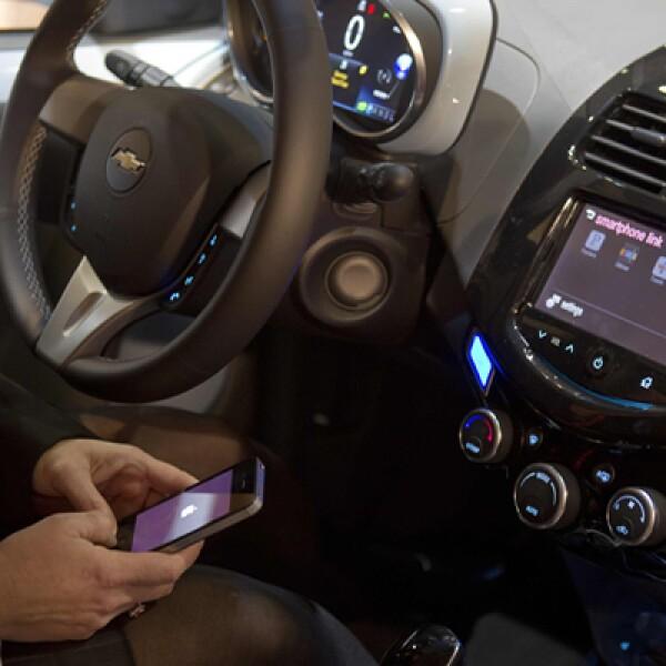 Firmas automotrices también participan en el evento. Una mujer enlaza su iPhone al sistema MyLink de un Chevrolet Spark.