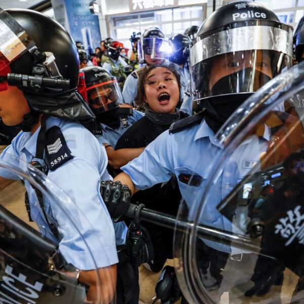 Riot police detain a woman as anti-government protesters gather at Sha Tin Mass Transit Railway (MTR) station to demonstrate against the railway operator, which they accuse of helping the government, in Hong Kong