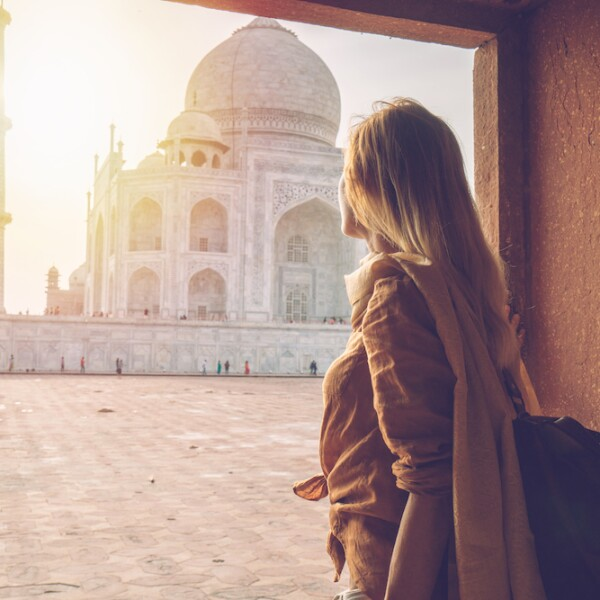 Beautiful blond hair girl contemplating sunrise at the Taj Mahal in India