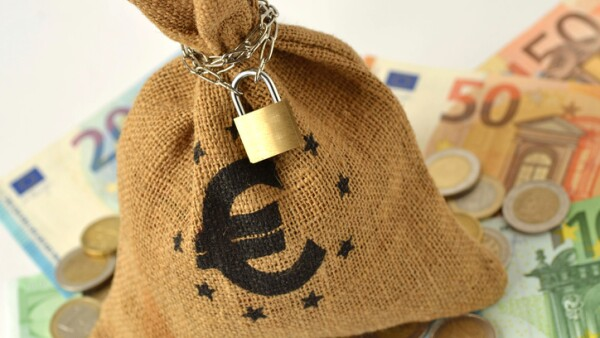 Money bag with padlock and chain over euro banknotes and coins - Saving money and financial security concept