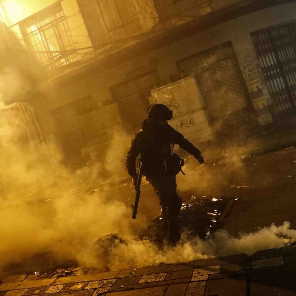 Demonstrators hide behind a makeshift barrier during a protest in La Paz