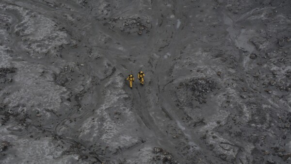 Rescue crew dressed in protective gear are seen as they work to to retrieve bodies on the volcanic White Island in New Zealand