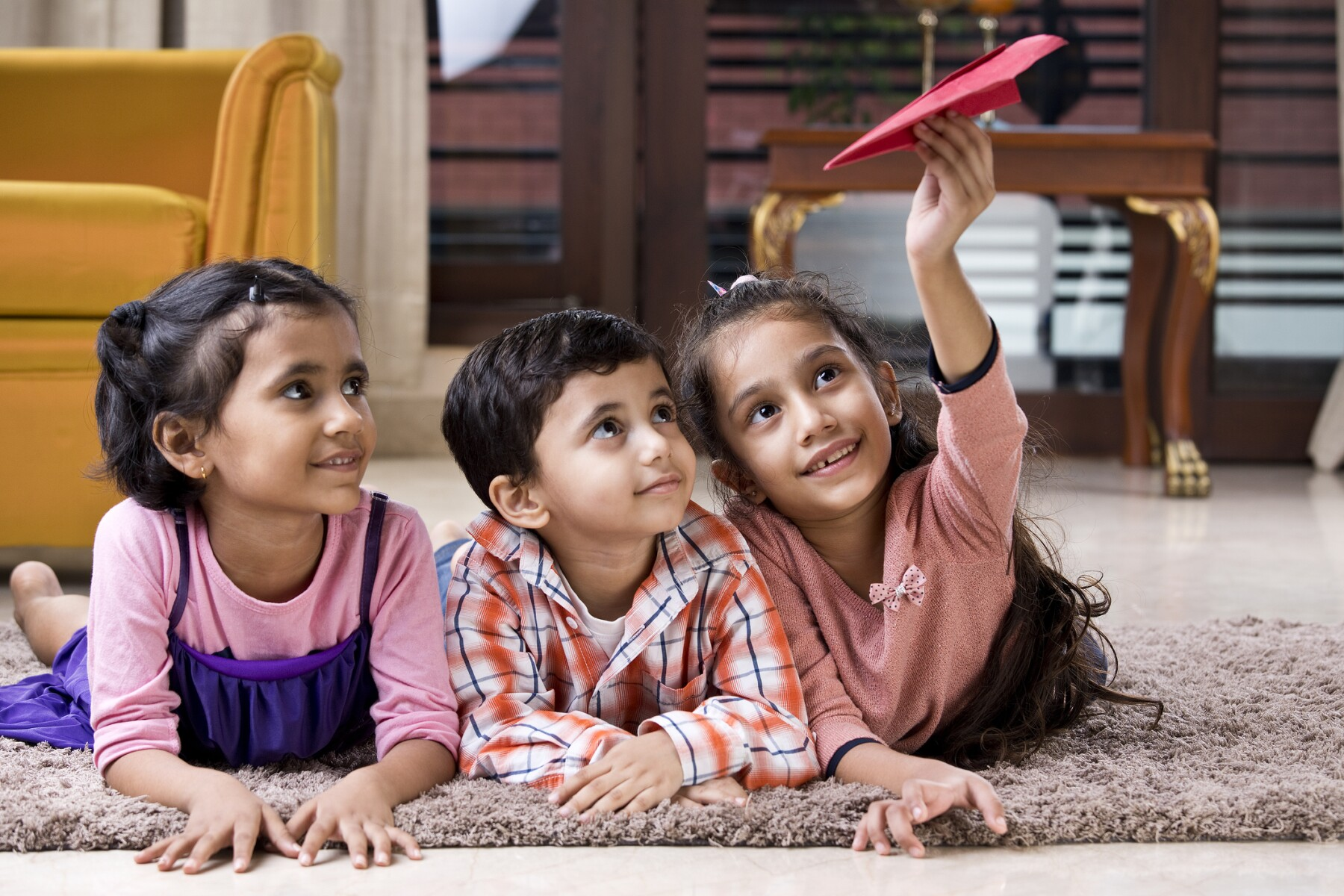 Children playing with paper airplane at home