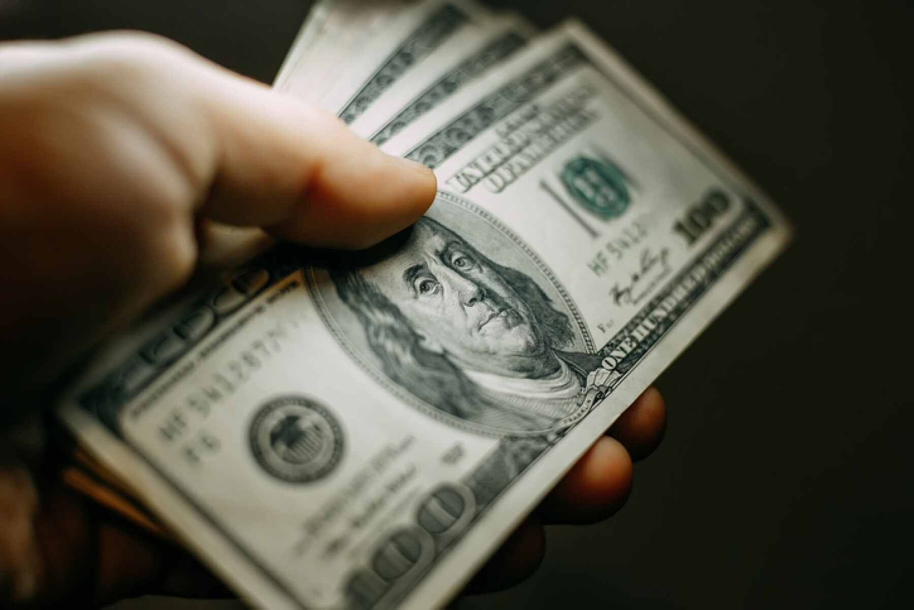 Man hand with a stack of hundred US dollars bills, close up