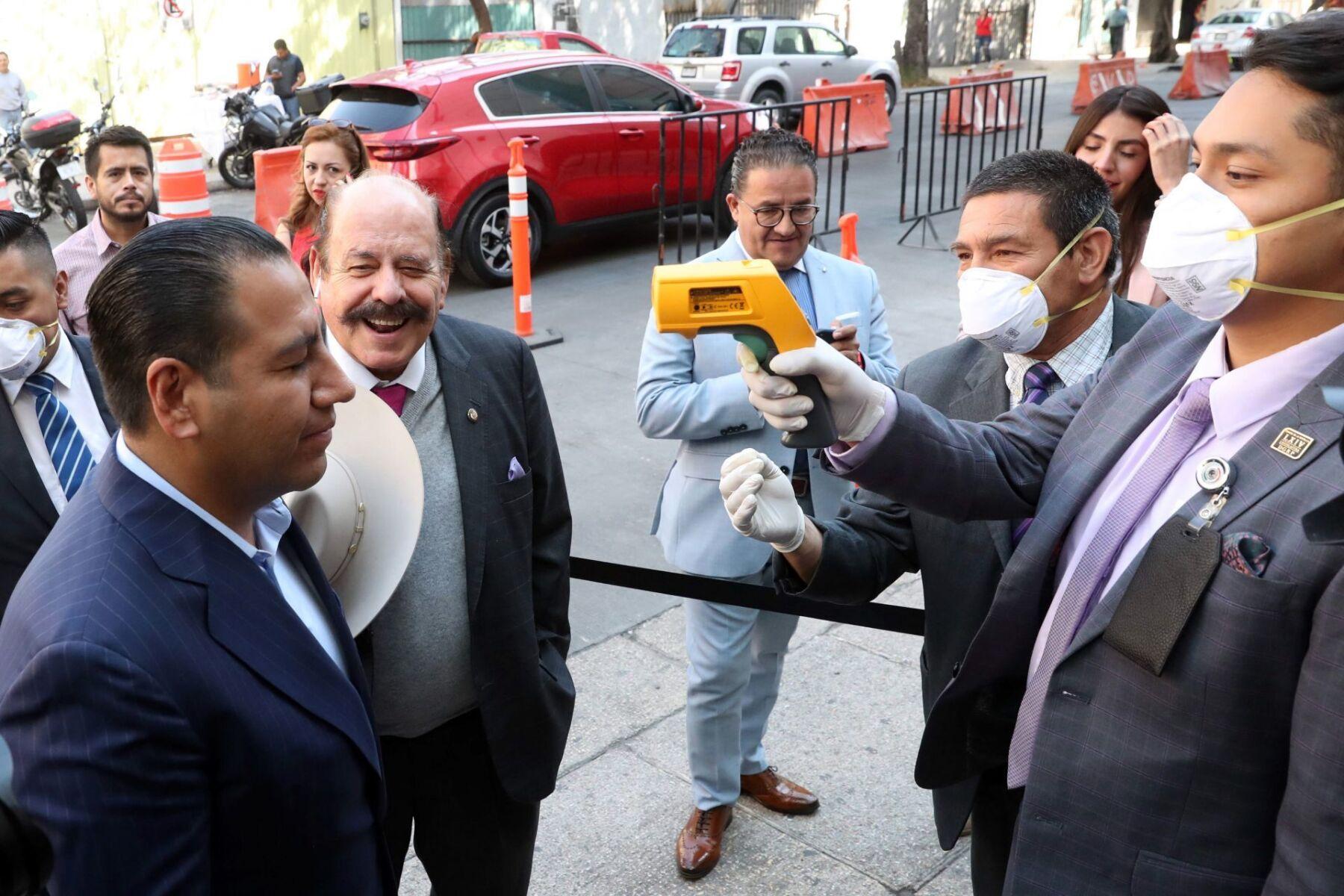El senador Óscar Ramírez es revisado con el termómetro digital como medida preventiva ante el Covid-19