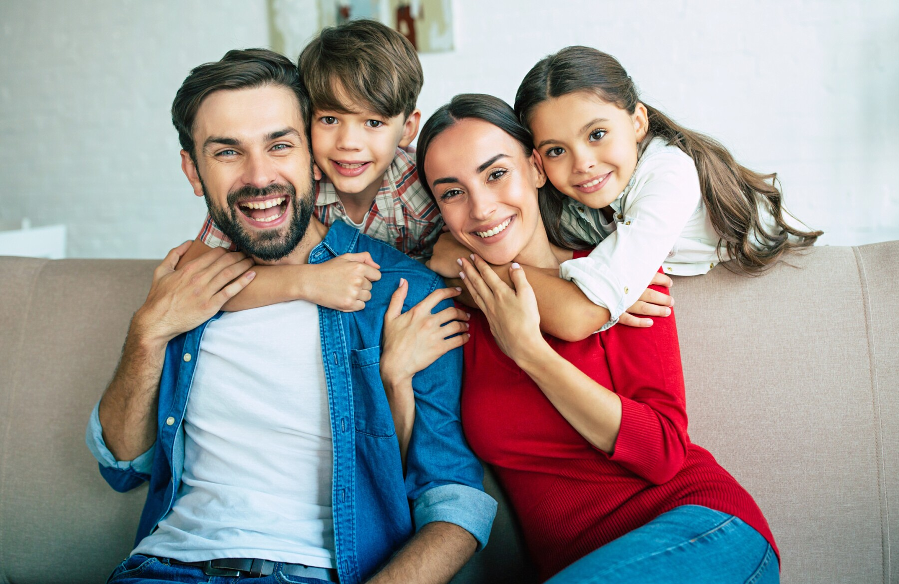 Young happy family relax together at home smiling and hugging