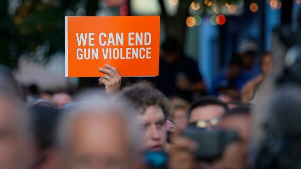 A vigil attendee holds a sign during a vigil at the scene of a mass shooting in Dayton