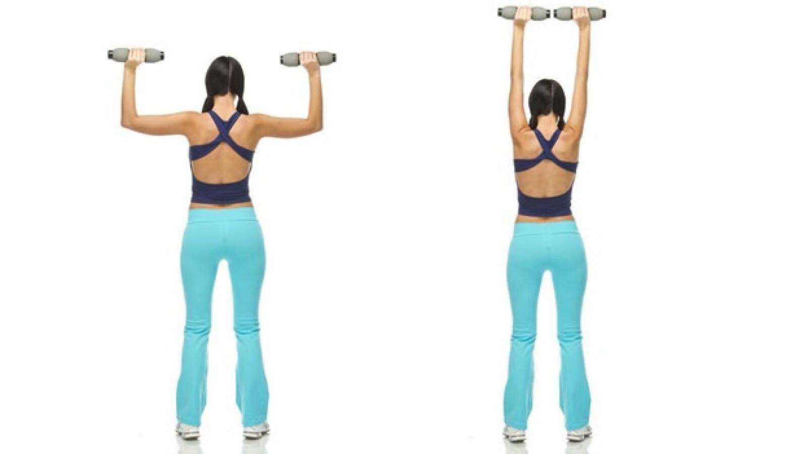 1. Toma las mancuernas a la altura de los hombros y empuja hacia arriba hasta tener los brazos estirados, baja de manera controlada y repite
