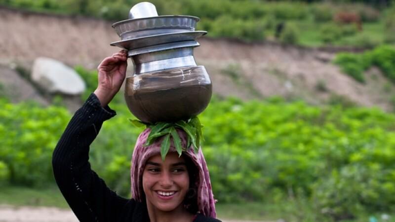 una joven en cachemira lleva agua