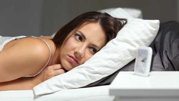 Sleepless insomniac girl looking at alarm clock in the night
