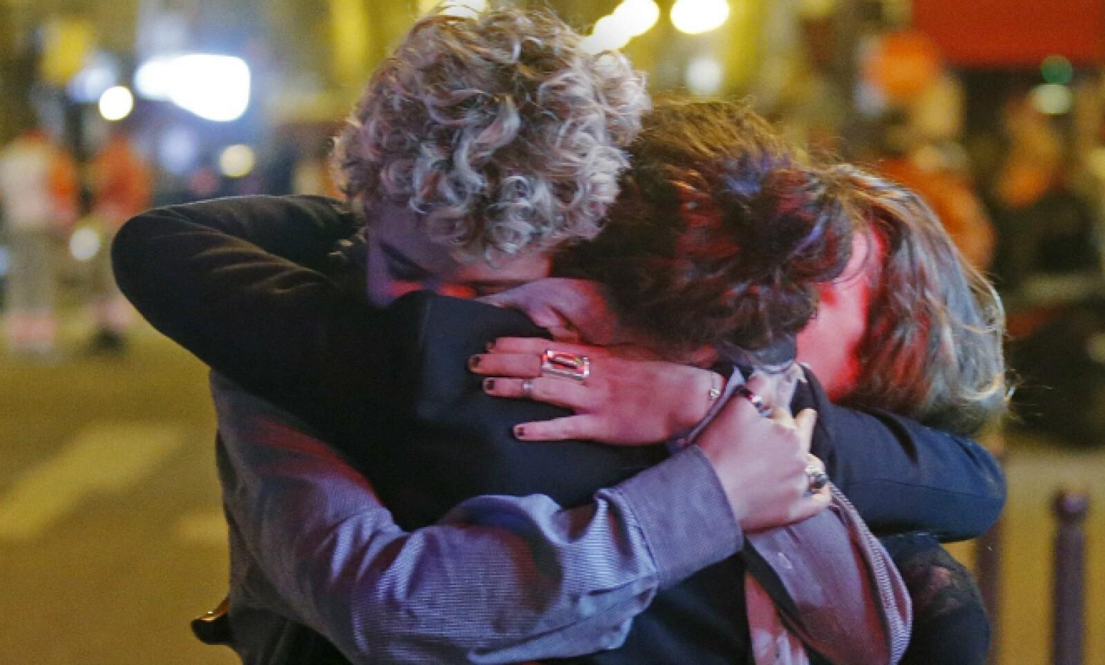 Un grupo de personas se abrazan al salir del teatro en el que más de 100 personas murieron.