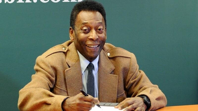 Pelé firma una copia de su libro 'Why Soccer Matters' en Nueva York el 1 de abril