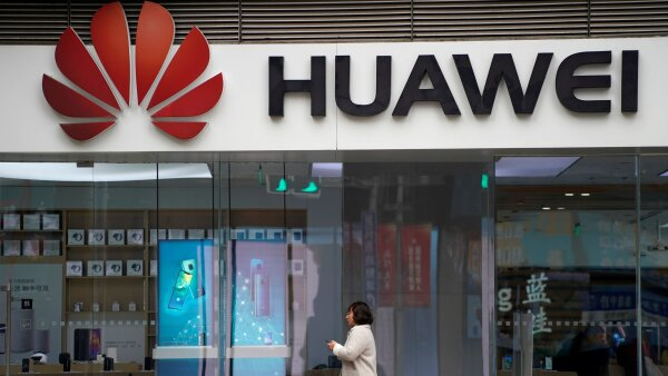 FILE PHOTO: A woman walks by a Huawei logo at a shopping mall in Shanghai