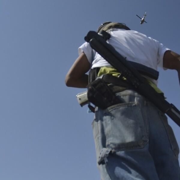 Un integrante de autodefensa vigila mientras un helicóptero sobrevuela el municipio