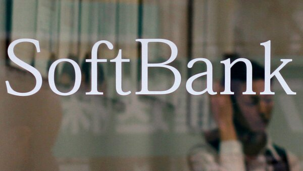 FILE PHOTO: An employee works behind a logo of Softbank Corp at its branch in Tokyo