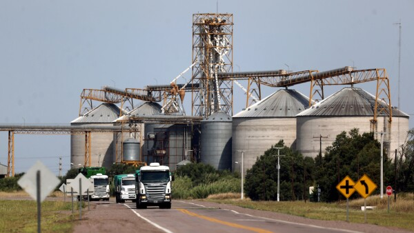 FILE PHOTO: Trucks pass by grain silos near Ceres