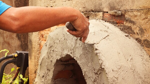Worker were plastering with trowel putty knife on construction site.