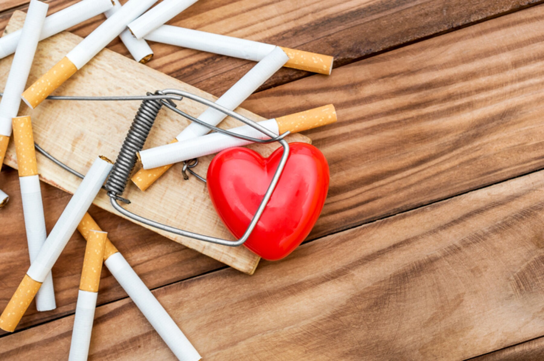 Red heart in mousetrap with cigarettes on the wooden background. Top view.