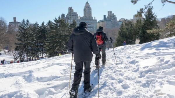 Una pareja sacó sus esquíes y calzado para la nieve para 'viajar' por Central Park, en Nueva York, mientras el sol dura este domingo.