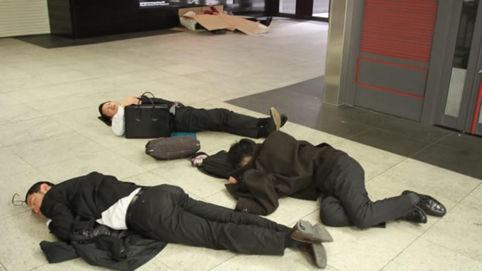 Oficinistas japoneses duermen en una estación de tren tras el terremoto