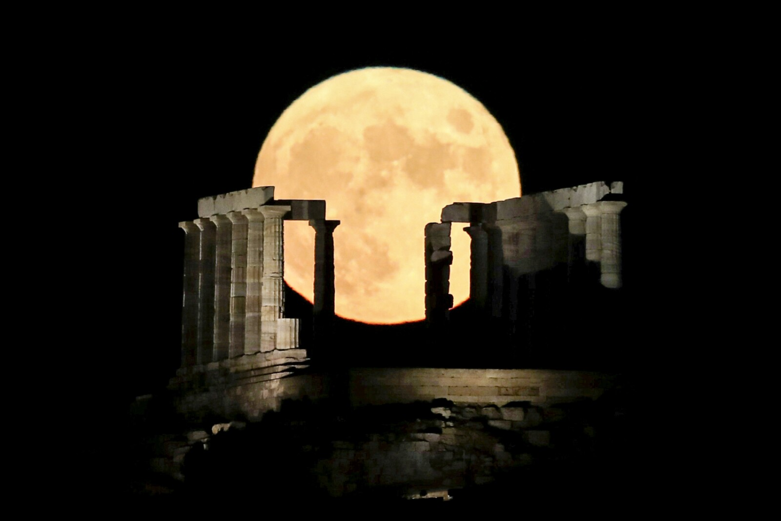 A full moon rises behind the Temple of Poseidon in Cape Sounion, near Athens