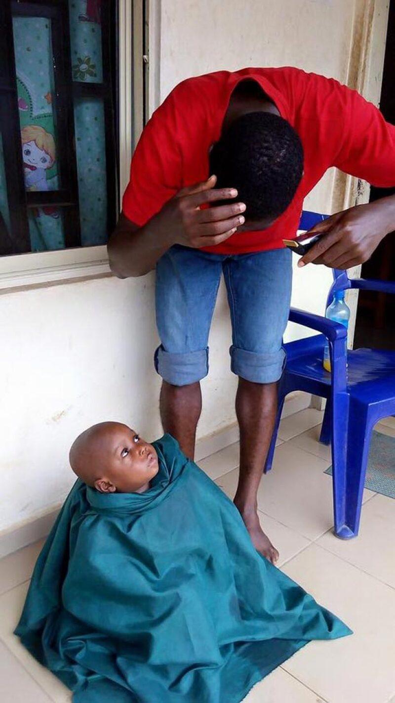 El pequeño recibiendo un corte de pelo en el orfanato.