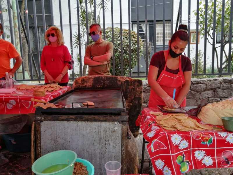 Clientes esperan a 1.5 metros del puesto de Guadalupe Hernández para recibir sus quesadillas y sopes en el mercado sobre ruedas de Plateros, en Álvaro Obregón.
