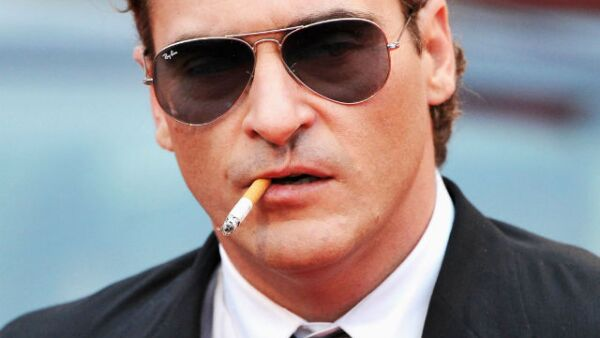 Joaquin Phoenix fumando y portando lentes oscuros. Un galán con aire de misterio.
