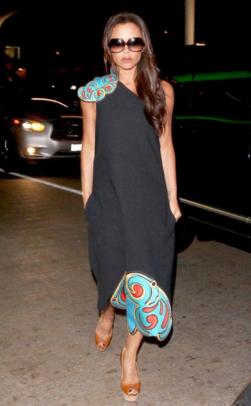 La ex Spice Girl fue capatada en el aeropuerto de Los Ángeles como la estrella que es, luciendo elegante en un costoso vestido de su propia línea de ropa.