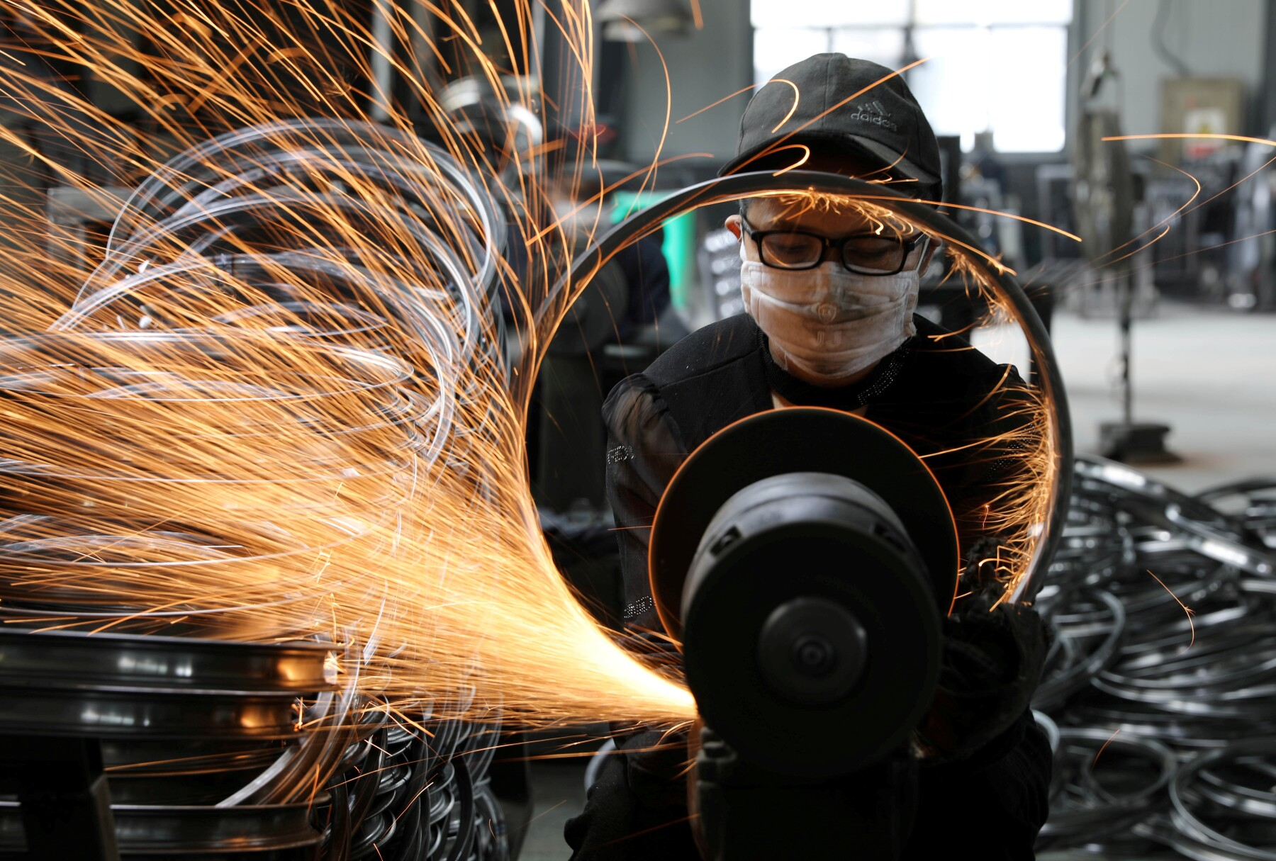 Worker welds a bicycle steel rim at a factory manufacturing sports equipment in Hangzhou, Zhejiang