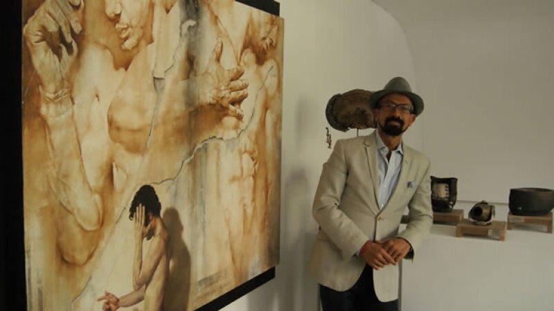 Óscar Román y alguna de las obras de arte expuestas en su galería.