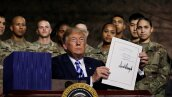U.S. President Trump holds up the National Defense Authorization Act after signing it in front of soldiers at Fort Drum, New York
