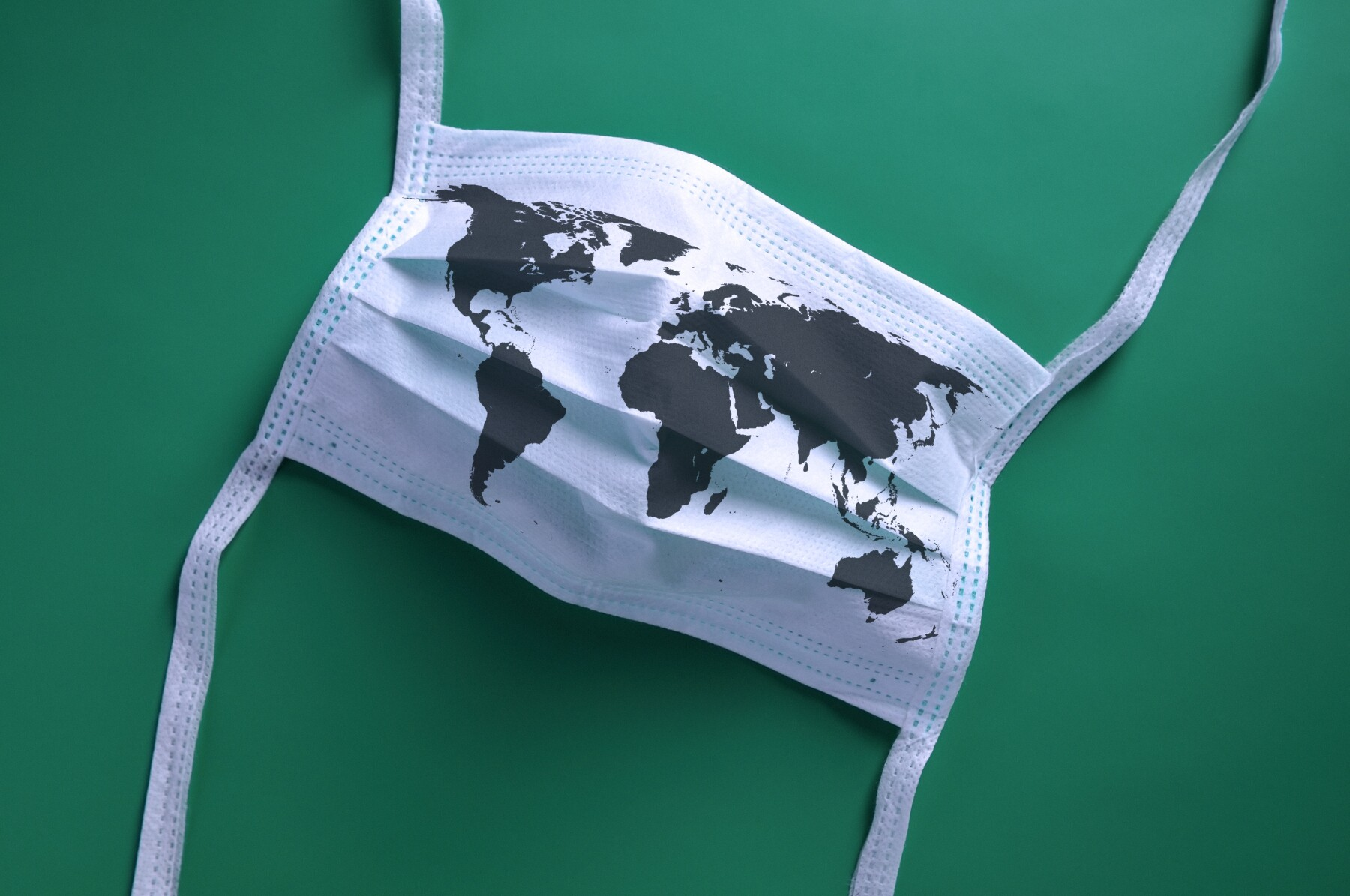 White face mask with a map of the world is lying on a green background