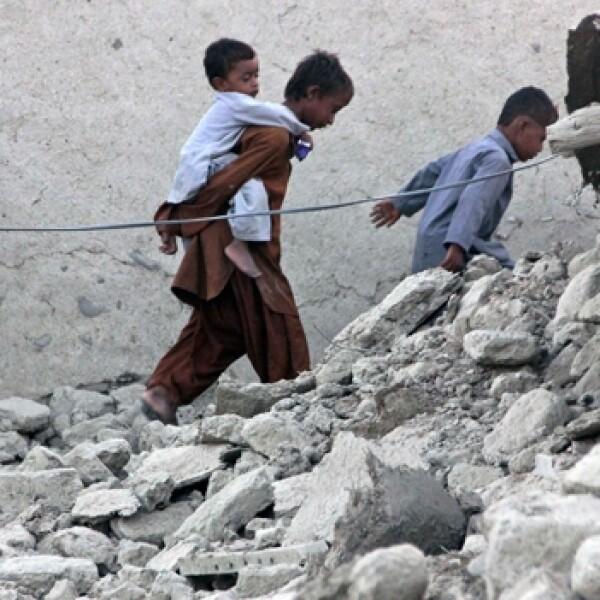 sobrevivientes caminan por los escombros de una casa