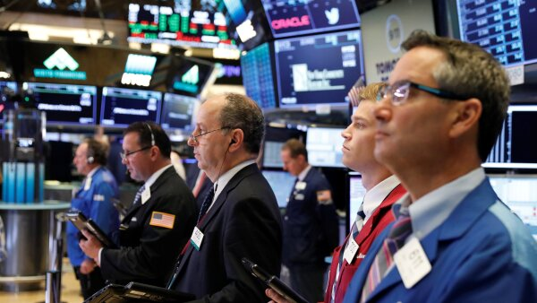 Traders pause for a moment of silence marking the 17th anniversary of the September 11, 2001 attacks on the World Trade Center on the floor of the New York Stock Exchange shortly before the opening bell in New York