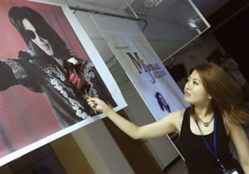 Una taiwanesa seguidora de Michael Jackson acerca una rosa blanca a un retrato del astro (AP).