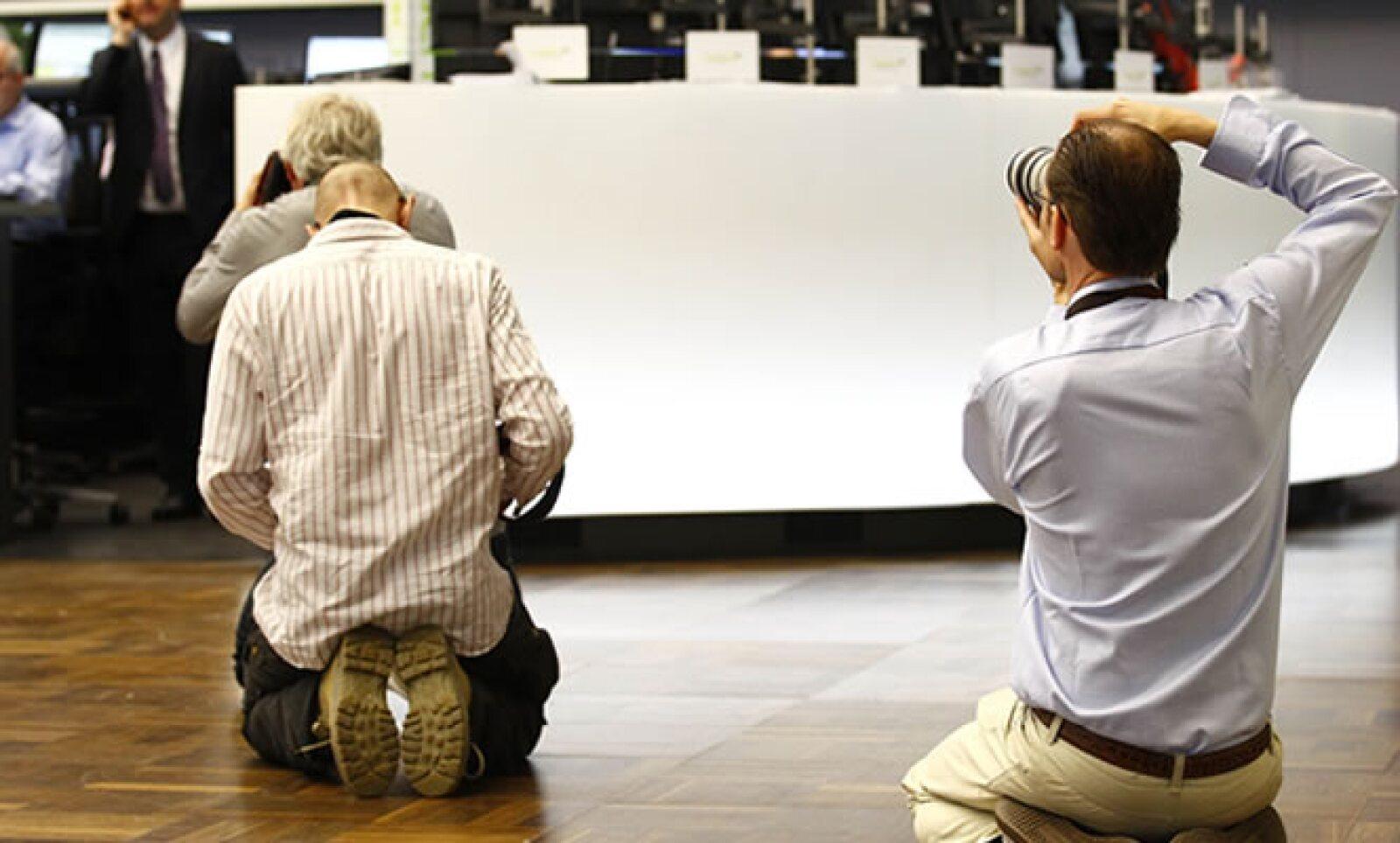 Reporteros gráficos buscan el mejor lugar para capturar las reacciones en la Bolsa de Frankfurt tras la rebaja  de nota de deuda de EU.